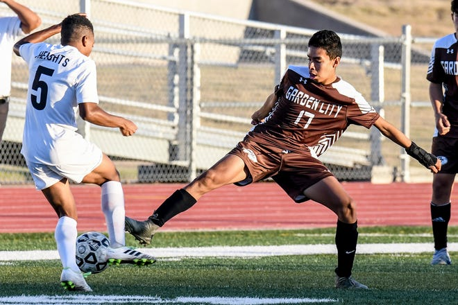 Garden City High School's Chris Barragan, right, knocks the ball away off the dribble of Wichita Heights Khaai Wilson Monday at Buffalo Stadium.  The Buffaloes shut out Liberal on the road Tuesday.