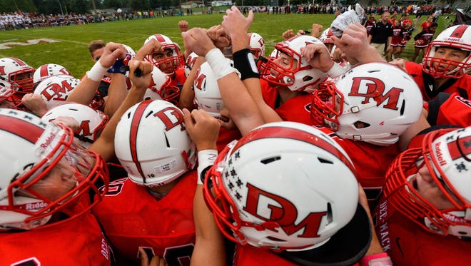 Dee-Mack High School football players huddle before the a 2016 game at Mackinaw.