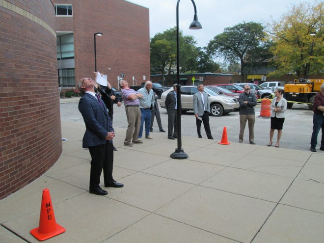 Monroe County Administrator Michael Bosanac (left) and other viewers look up to follow the flight of a large drone demonstrated by the Monroe County Sheriff's Office Tuesday in the parking lot at the county courthouse.