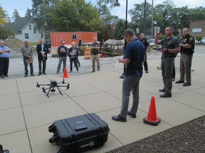 Monroe County Sergeants Dave Raymond (foreground) and Brian Francisco and Sheriff Troy Goodnough demonstrated the use of a large drone in the parking lot at the county Courthouse Tuesday afternoon. The aircraft rose to almost 400 feet and was used to target vehicles passing over the S. Monroe St. bridge a few blocks away.