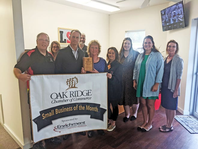 Owner Chip Morton, left, is joined by award sponsor Craig Peters of Enrichment Federal Credit Union, and his wife Debra to accept the award. Also pictured are members of the Life Safety staff and Oak Ridge Chamber of Commerce representatives.
