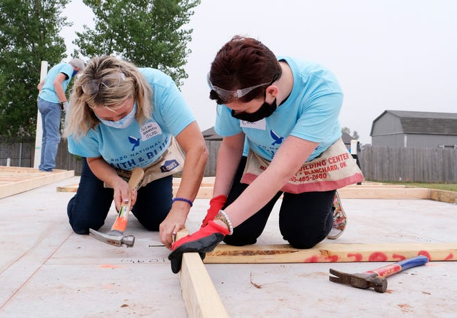 Oklahoma City Police Capt. Susan Kennedy and Kimley Deutsch of Life.Church nail studs for a wall during a Habitat for Humanity project in Yukon, held as part of the 2020 Faith and Blue Weekend.