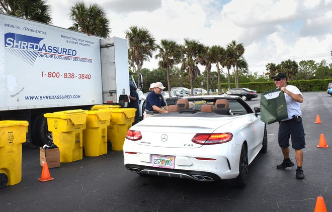 Jack Cohen, left, and Officer Jim Miller collect material to be shredded in 2017 at Phipps Ocean Park.