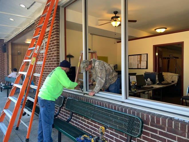 Two workers from Bonfert Glass Co. work Thursday, Sept. 30, 2021, on framing for new windows at Alliance Community Pantry, 215. E. Market St. in Alliance.
