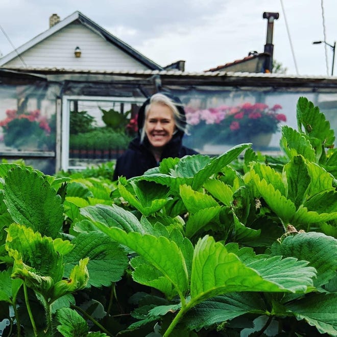 Sarah Stewart, executive director of Unity Gardens, is with some green friends. The gardens have been nominated for an award from USA Today.
