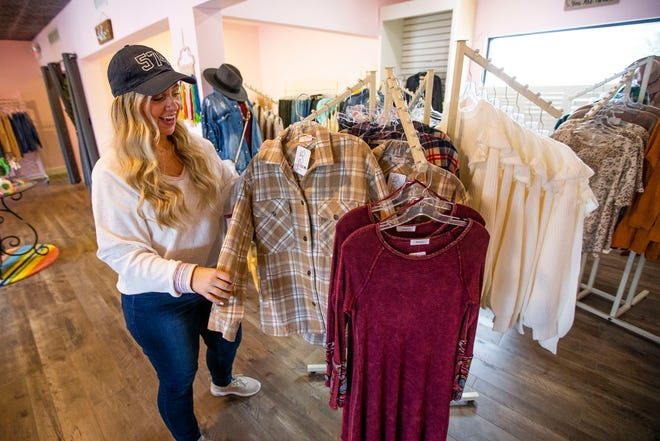 Kelsie Noble talks about available items Wednesday, Oct. 6, 2021 at the Pink Pineapple Boutique in Granger.