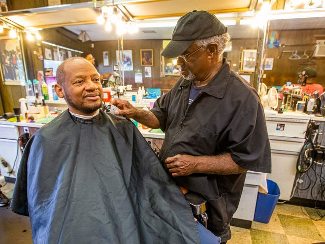Al Carothers, owner of Al's House of Style, gives a haircut to Dr. Carlton Lyons, of South Bend, on Tuesday, Oct. 5, 2021, inside Al's House of Style in South Bend.