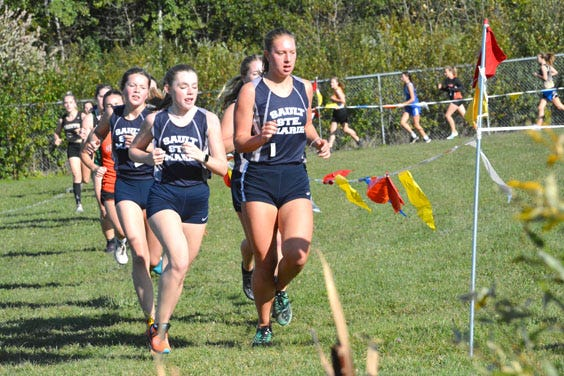 Sault High's Abigail Walther, left and Joanne Arbic, right, lead a group of runners at a home meet on the Lynn Trails course. The Blue Devils hosted two meets last week, including the Sault Elks Invitational Saturday.