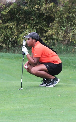 Madison Webb of Sturgis lines up a putt in regional golf action on Tuesday.