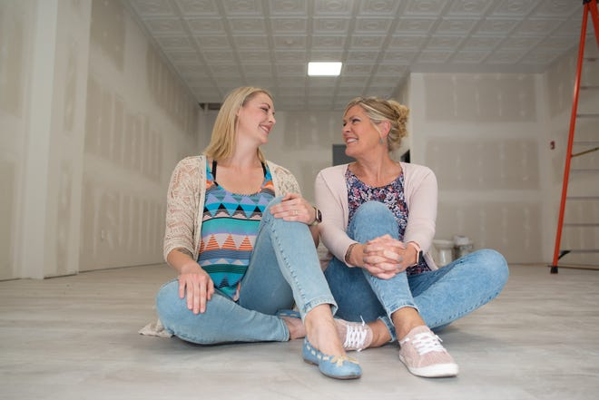 Topeka Yoga Network co-owners Evelyn Spangler, left, and Mary Boland  sit Wednesday morning in the storefront that will soon be home to their brick-and-mortar yoga studio.