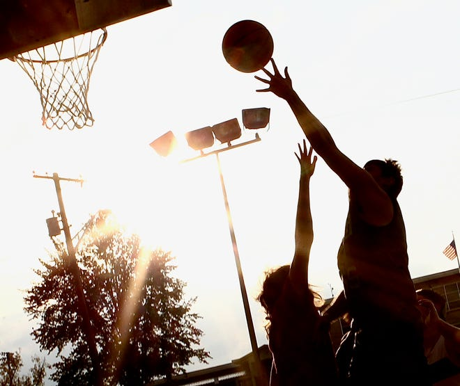 Ball players are silhouetted by the sun as they compete three on three at Thornton Park Tuesday evening.