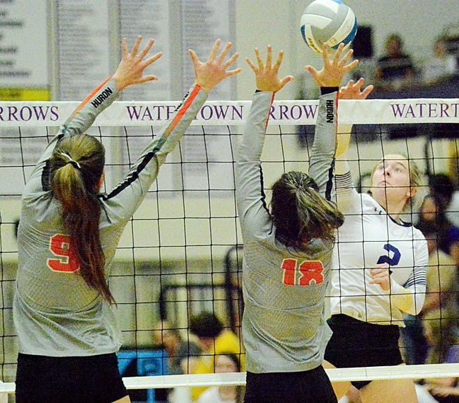 Watertown's Trinity Hodorff spikes the ball against Huron's Emily Dale (8) and Hamtyn Heinz (18) during their high school volleyball match Tuesday night in the Civic Arena. Huron won 3-0.