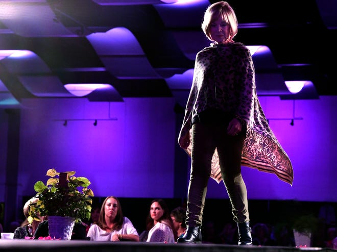 Jan McCarty is silhouetted as her garment billows behind her during Tuesday's Fashions for the Cure at the Abilene Convention Center.