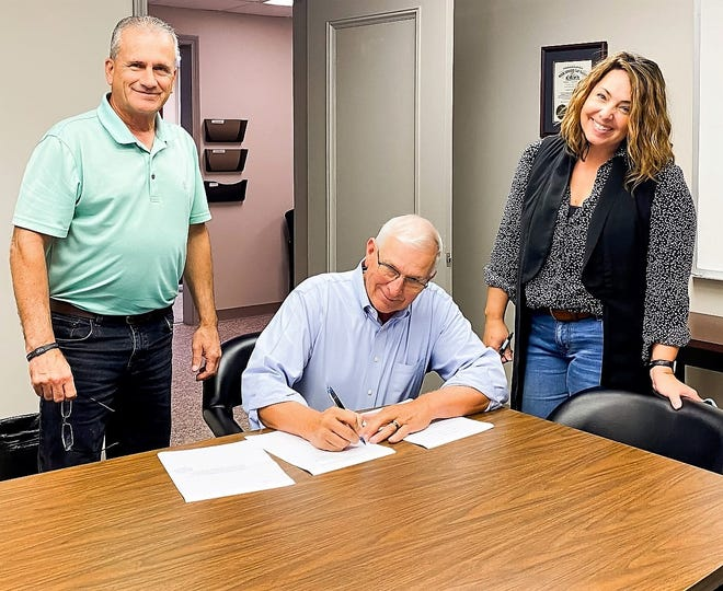 Commissioner Dane Shryock, seated, with Commissioner Gary Fischer and Coshocton Port Authority Director Tiffany Swigert, signs an agreement between the county and the Ohio Public Works Commission for a Clean Ohio Green Space Conservation Program grant of $143,060. Money will go toward the Three Rivers Peninsula project, turning the former Skip's Refuse into green space for the community.