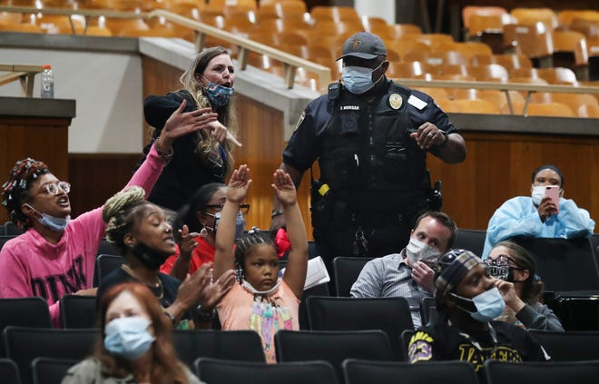 A security officer tried to calm the audience after some began shouting and disrupted a JCPS school board meeting at Central High School Louisville, Ky. on Oct. 5, 2021.