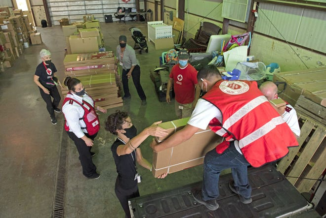 olunteers from the Salvation Army and the Red Cross unload shelves in a warehouse at Holloman Air Force Base, New Mexico, Sept. 4, 2021.