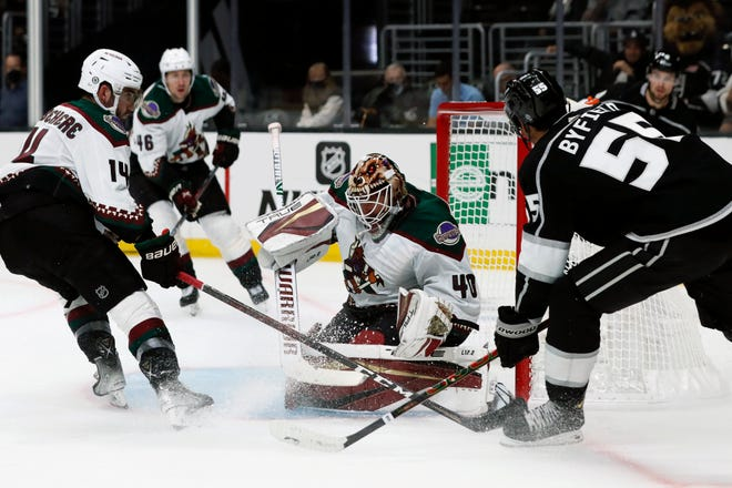 Arizona Coyotes goaltender Carter Hutton (40) stops a shot by Los Angeles Kings center Quinton Byfield, right, with defenseman Shayne Gostisbehere (14) defending during the second period of a preseason NHL hockey game in Los Angeles, Tuesday, Oct. 5, 2021.