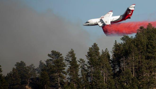 A heavy air tanker drops retardant onto the Auburn Fire near Deadwood Avenue on Tuesday, Oct. 5, 2021, in Rapid City, S.D.
