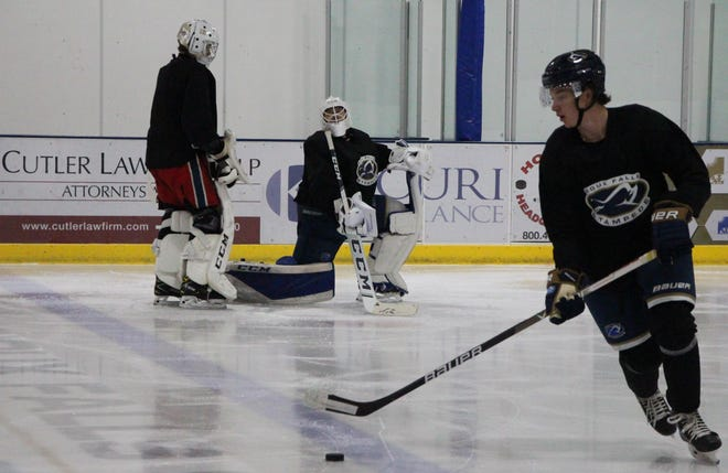 Stampede forward J.P. Turner circles the puck while goalies Michael Sochan (standing) and Noah Grannan stretch before practice Wednesday at the Ice Plex