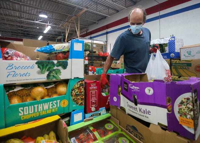 Kelley Jones bags food for distribution on Monday at The Neighbors' Place in Wausau.