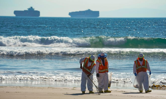 A cleanup crew walk along Huntington Beach looking for spots of oil north of the pier with cargo container ships in the background. More than 125,000 gallons of oil spilled from a pipeline about four miles offshore of Southern California's coast. The spill left a sheen over miles of ocean along the shoreline at Huntington Beach.