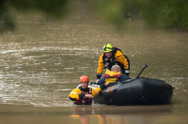 In this October, 2015 file photo, Austin firefighters  rescue a man from the Onion Creek neighborhood. [JAY JANNER / AMERICAN-STATESMAN]