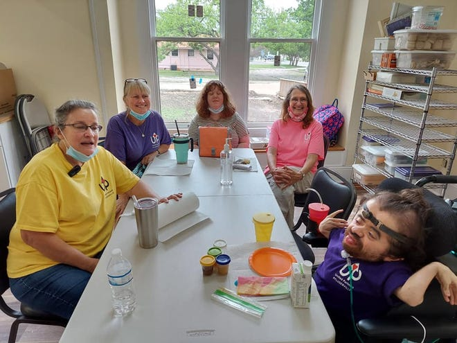 Volunteers at United Partners in Pflugerville gather at the table for arts and crafts. The nonprofit received a Gannett Foundation grant of $2,500 this month.