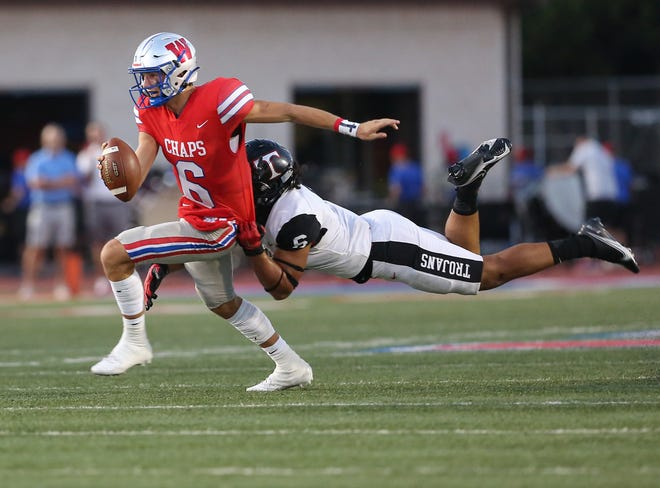 Westlake quarterback Cade Klubnik, left, escapes Trinity's Nai Mose in a game earlier this season. Klubnik and the No. 1 Chaps host Bowie in a battle of unbeatens Friday at Chaparral Stadium.