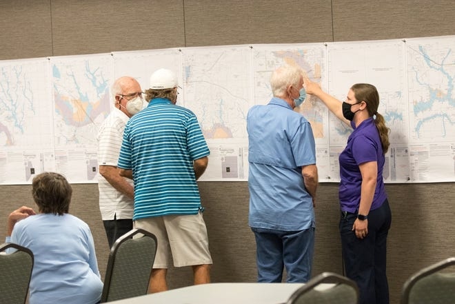 Allison Land, at right, with the city of Bastrop's Planning Department, explains the new proposed floodplain maps to county residents on Monday at the Convention Center.