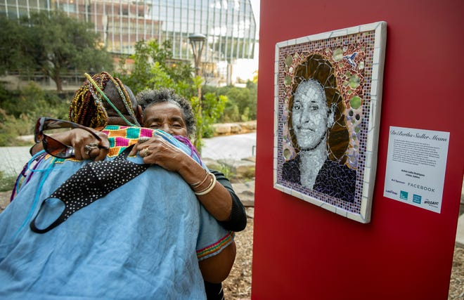 Janet Means Scott, right, of San Antonio, hugs Lolita Rodriguez at a ceremony Thursday at the Austin Central Library, where Latinitas honored trailblazing women of color, including Janet's mother, Bertha Sadler Means, with mosaic portraits. Rodriguez is the artist who created the portrait of Means.