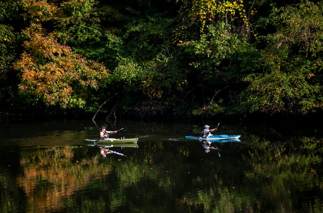 Kayakers and the changing colors of leaves above them are reflected in the lake at Bradys Run Park Wednesday.