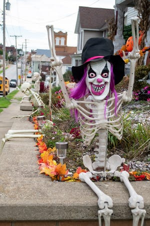 Decorated for Halloween, a home on Main Street is lined with pumpkins and waving skeletons.