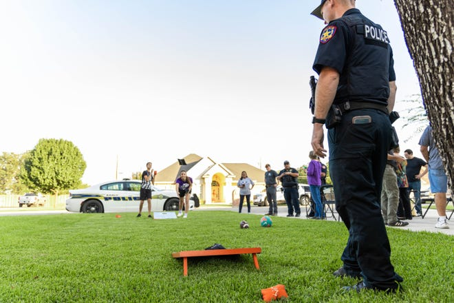 Early police officer Marvin Simpson stands in a lawn on Rainbow Drive in Early during a game of cornhole during National Night Out Tuesday. Block parties were held in multiple locations in Brownwood, Early and rural Brown County.