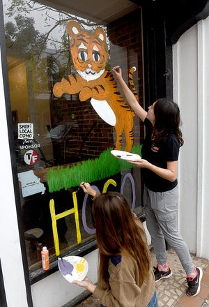 Madeline Ewing, left, and Alana Hatanaka, both members of Phi Sigma Pi fraternity, paint the window of Bubble Cup Tea Zone on Thursday at 23 S. Ninth St. Dozens of fraternity and sorority members painted downtown business windows to celebrate University of Missouri Homecoming this week.