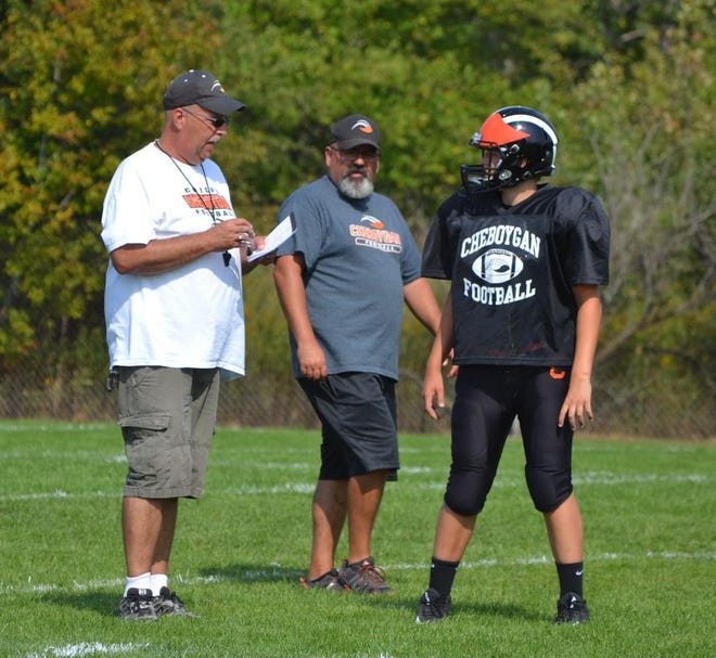 Cheboygan junior varsity football coach Scott Kelley, left, chats with coach James Seaman, middle, and a player during a practice from the 2020 season. After over 30 years with the program, Kelley stepped down as Cheboygan's JV head coach following last season.