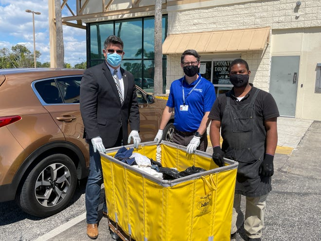 Orlando Commissioner Tony Ortiz,  Goodwill Industries of Central Florida president and CEO Ed Durkee and a Goodwill employee fill a donation bin during Goodwill's Be A Good Neighbor initiative on Sept. 28.