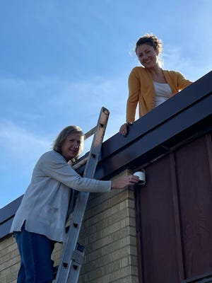 Angela Bartholomay on the ladder, Janelle Green on the roof showing sensor and air map samples.