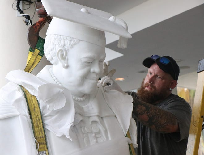 Mark Wilkerson with Hutchinson United Rigging adjust the rigging for the move to the pedestal, Wednesday October 6, 2021 at the News Journal Center .