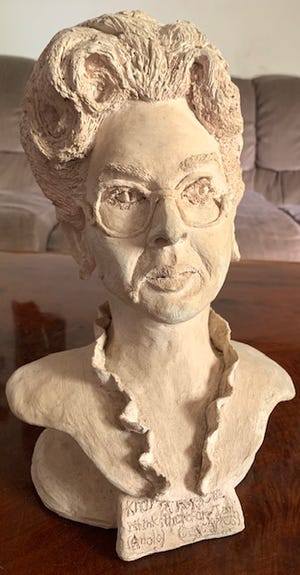 Chuck Mills' mother, able to use only her left hand, carved this urn  in her own likeness by looking in a mirror.