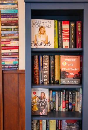 Los libros están apilados en los estantes, y empotrados en la pared, en Archive Book Cafe en Fall River.