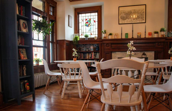Las mesas y sillas están colocadas alrededor de la chimenea dentro del Archive Book Cafe en Fall River.