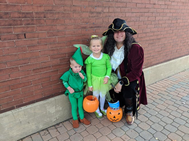 A family from Neverland poses for a photo in downtown Holland during the city's annual trick-or-treating event.