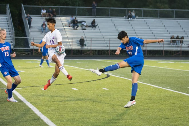 North Henderson's Dylan Perez (19) blocks the kick from West's Irbin Villafuerte in Wednesday's match at West.