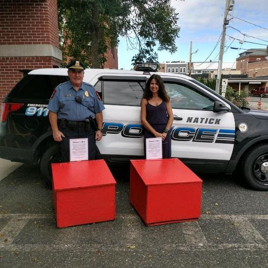 """Natick Auxiliary police Capt. Patrick Irr, left, and Tara Caramanica, of Boylston, pose with the town's new Manny's Boxes. Caramanica and several other Boylston residents make the boxes in honor of Worcester police officer Emanuel """"Manny"""" Familia, who drowned in June while trying to save a teenage boy."""