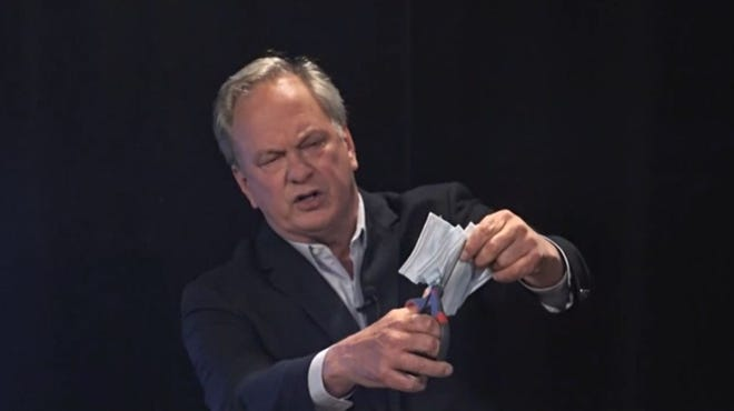 Max Linn uses scissors to cut through face masks during a televised debate Sept. 28, 2020, in Maine's contest for U.S. Senate. Linn became known for his debate antics during the four-way campaign, in which he finished last behind Republican Sen. Susan Collins, who won reelection, and Democrat Sara Gideon and independent Lisa Savage.