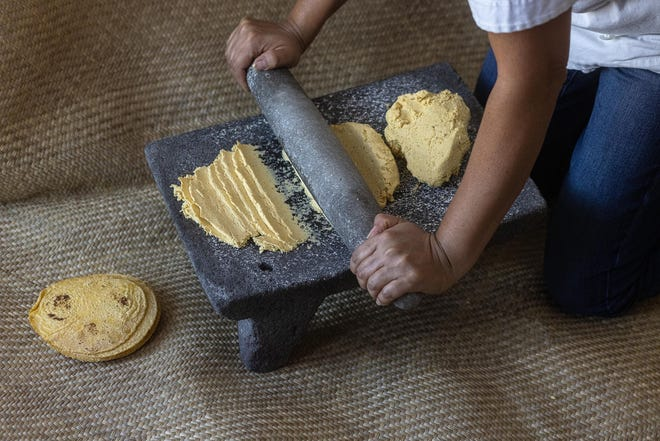 Chef Aurora Garcia Ramos kneads corn masa for tortillas on the metate stone she inherited from her grandmother in Puebla, Mexico.