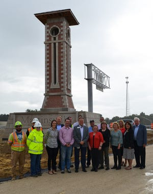 Representatives from INDOT, Walsh Construction, the city of Martinsville, Morgan County, the state and the aesthetics committee that helped design the monument gather for a photo in front of the Ind. 44 monument on Martinsville's north side on Thursday.
