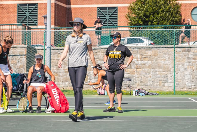 Ashleigh Antal walks on the court to catch up with some players with assistant Miller Hales behind her during a match against Coastal Carolina.