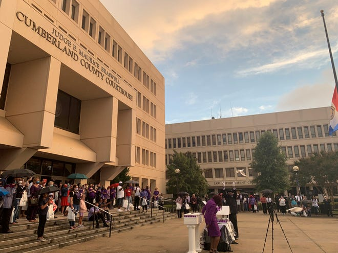 People gathered outside the Cumberland County courthouse watching the dove release at the end of the 'Remember My Name' Domestic Violence Vigil.