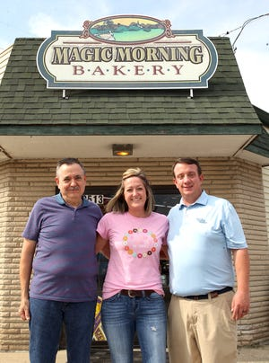 Departing Magic Morning Bakery co-owner Scott Stroud, (with wife Laura Stroud, who could not be present for the picture), new co-owners Emily Fortner, and Andy Fortner pose in front of Magic Morning Bakery at 2513 16th St. Thursday.